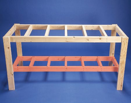 <b>Photo 3: Lower frame</b></br> Flip over the bench and attach the lower shelf frame. Use gallon paint cans to support the lower shelf frame when you're attaching it to the main workbench legs.