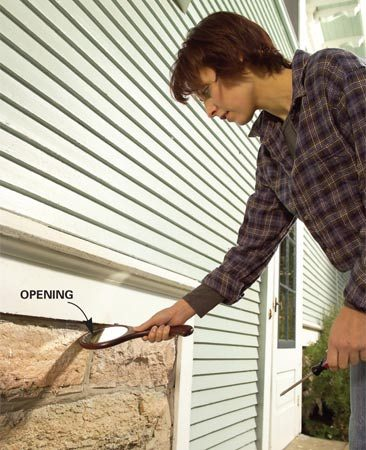 <b>Inspect the area below your siding</b></br> Inspect the underside of your siding using a mirror. If you find a gap, mark the location with masking tape so you can seal it later.