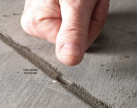<b>Test the grout with your fingertips</b></br> Our expert says that one of the biggest mistakes you can make on a grout job is to start cleaning up the grout too soon. Wiping the grout before it's hardened a bit allows too much water to penetrate the surface. That means blotchy-looking grout or, worse, hairline cracking and grout that falls out. To avoid these problems, be sure the grout is very firm, about like a wine cork, before you start cleaning it. Press your fingertip into the grout to test it. If it dents easily, wait.