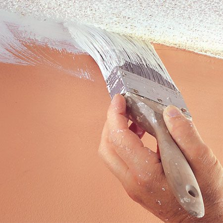<b>Use a 3-in. brush to cut in ceiling edges</b></br> Cut in the perimeters of ceilings with ceiling white and a 3-in. brush. Don't worry if you lap over onto the wall. Roll on a second coat of ceiling paint in the opposite direction of the first coat.