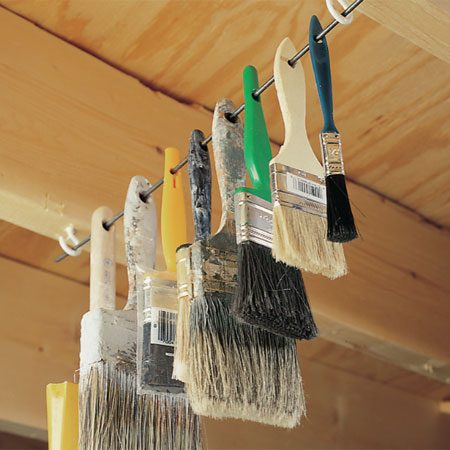 <b>Hang brushes on a rod or wire</b></br> Hang your paintbrushes out of harm's way by installing a couple of screw eyes or cup hooks on the bottom of a couple of rafters or floor joists. Then thread the brush handles through a stiff wire (or welding rod) and hang it all up.