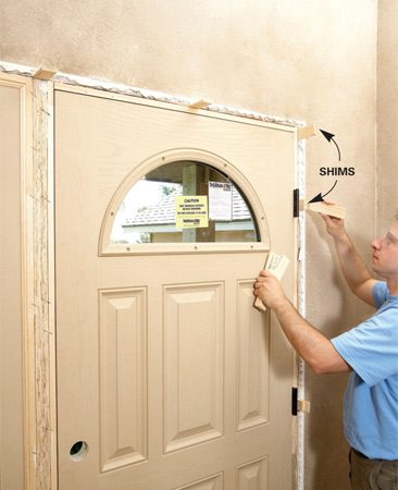 <b>Photo 10: Shim the door frame</b><br/>Danny slid pairs of shims behind the hinges and along the sidelight on the opposite side. He positioned the shims to create an even gap around the door.