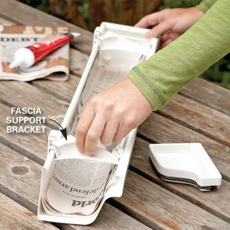 <b>Photo 2: Assemble the parts</b></br> Slide both fascia support brackets onto the gutter and glue the other end cap into place.