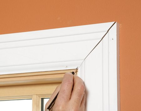 <b>Photo 1: Mark the gap size</b><br/>Cut the moldings at a 45-degree angle. Hold the miter together to see how it fits. If there's a gap, estimate how much you'll have to trim off to close the gap, and make a mark where the moldings touch.