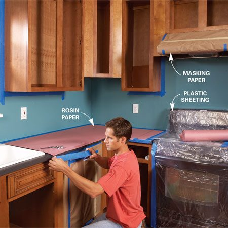 <b>Photo 2: Protect adjoining surfaces</b></br> Tape off the walls, ceiling and flooring, and cover the countertops with rosin paper. Wrap appliances and the vent hood with plastic sheeting or masking paper.