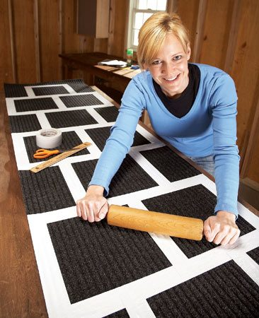 <b>Photo 1: Tape the lines</b></br> Use a rolling pin or wooden dowel to press the duct tape down firmly so it doesn't come off when you roll up the mat to store it.