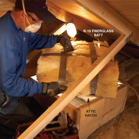 """<b>Photo 3: Insulate access doors</b></br> <p>Cover the attic   hatch with a   pillow of fiberglass   insulation. """"You   want a nice, big   puffy pillow of insulation   to stop any air   leaks,"""" says Olson.   Cut two layers of   R-19 fiberglass batt   insulation slightly   larger than the   hatch and staple   duct tape to the   hatch edges to   secure it in place. </p>"""