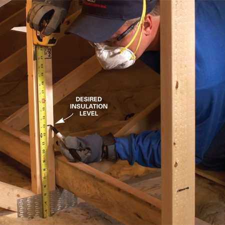 <b>Photo 4: Mark reference lines</b><br/>Measure up from the drywall to mark your desired insulation level. Use a permanent marker to mark the level every few trusses so you know you have even coverage around the entire space.