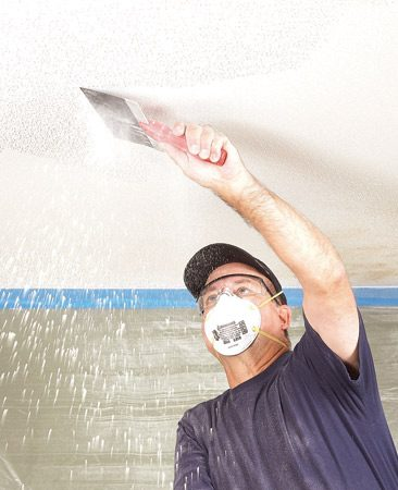 <b>Photo 2: Scrape the ceiling</b></br> Suit up with goggles, a dust mask and a hat before you start the messy job of scraping texture. Popcorn spray texture comes off easily if it hasn't been painted.
