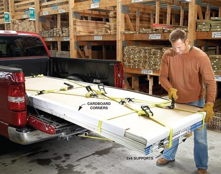 <b>Ratchet straps help you push the envelope safely</b></br> If you have a 6-ft. bed, you'll have to haul a large load of sheet goods with the tailgate down. We're showing you an extreme example by loading 4 x 12-ft. drywall in a 6-ft. bed. Start by laying out two ratchet straps across the truck bed. Then lay out at least two 12-ft. 2x4s to help support the overhang (check the load limit of your truck and the weight of each sheet). The 2x4s will also protect the drywall from any water, rocks or crud on your truck bed. We scrounged up some cardboard corners to protect the edges of our drywall (check the trash bins in the store or lumberyard). Then tighten the bottom straps to secure the bundle. Next, run two straps from the truck bed anchor rings around the back edge of the sheets and down to the bumper.