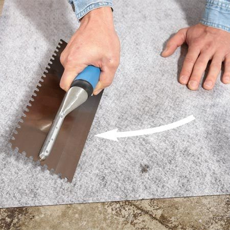 <b>Photo 4: Bond membrane to the floor</b></br> Push air bubbles out to the edge with a J-roller or the edge of a grout float. Then apply pressure to the entire membrane to complete the bond.