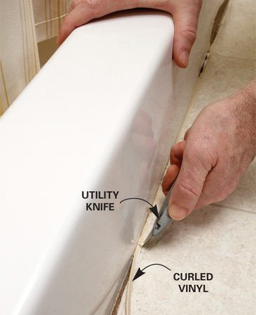 <b>Photo 1: Cur out the curled vinyl</b></br> Slice alongside the curled edge of vinyl flooring with a utility knife. Then peel off the thin strip of vinyl and clean out any dirt or old caulk.