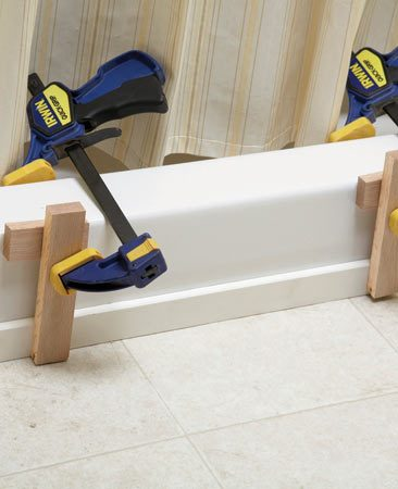 <b>Photo 3: Clamp the threshold</b></br> Press the threshold against the shower base. If there are gaps, use clamps to hold the threshold tight until the caulk sets.