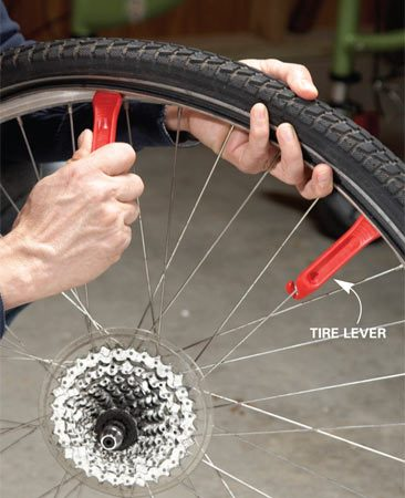 <b>Photo 1: Remove the tire</b></br> Pry under the bead of the tire with one of the tire levers and hook it to a spoke. Move over about 4 to 6 in. and insert the other tire lever. Pry it down and then slide it along the rim to release the tire.