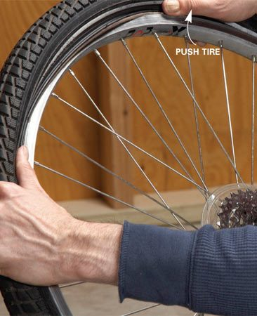 <b>Photo 3: Reinstall the tire</b></br> Press the tire back over the rim, being careful not to pinch the tube. If it's too tight to push the last section by hand, use the tire levers to pry the tire onto the rim.