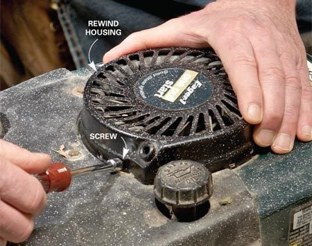 <b>Photo 1: Remove the rewind unit</b></br> Remove the screws that hold the rewind to the engine and lift it off. Use a nut driver to remove hex head screws.