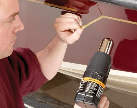 <b>Photo 1: Remove old numbers and pinstripes</b></br> Set the heat gun to a low setting and peel off the old decals and numbers. Use adhesive remover to get rid of any residue.