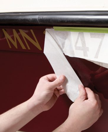 <b>Photo 9: Apply new decals</b></br> Position the new boat numbers and tape the sheet in place. Then lift the sheet up, remove the backer and press each number individually. Don't try to apply them all at once—they'll wrinkle.