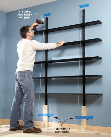 <b>Photo 7: Mount the bookshelf</b></br> Locate two studs that are 32 in. apart with a stud finder. Screw the standards to the studs, making sure the shelves are level and the standards are plumb.