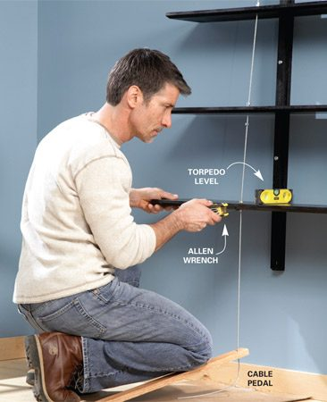 <b>Photo 8: Tension the cables</b></br> Tighten the cable using a scrap of wood with a hole in it to put tension on the cable while you tighten the setscrew on the collar below the lowest shelf. Then snug the remaining collars to the top and bottom of the shelves and tighten the collars.