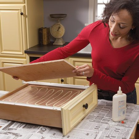 <b>Get the sag out</b></br> The thin plywood used for drawer bottoms sometimes gets wavy. Stiffen up the bottoms with 1/4-in. or 3/8-in. plywood. Cut the plywood to fit over the drawer bottom, leaving about a 1/4-in. gap on each side. Apply wood glue on the drawer bottom and set the plywood over it. Set a gallon or two of paint over the plywood to hold it in place until the glue dries.