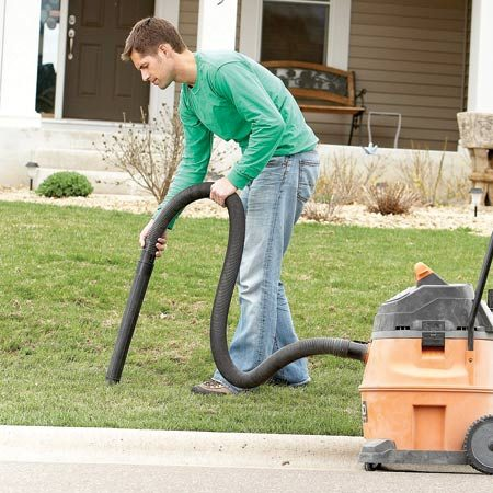 <b>Photo 1: Vacuum the pebbles</b></br> Gravel and sand hinder grass growth, so vacuum them up. Start along the street and vacuum into the yard until you no longer hear stones getting sucked up. Then do the same thing along the driveway.