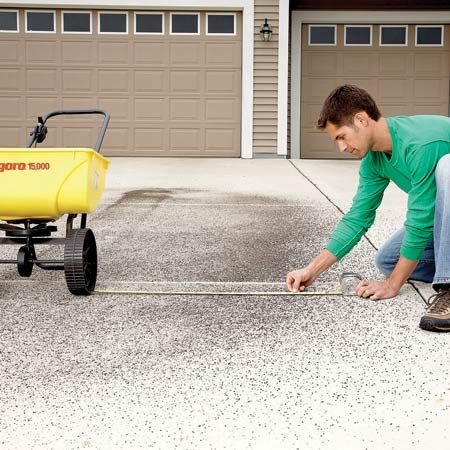 """<b>Photo 2: Check the spreader's """"throw""""</b></br> To apply the right amount of fertilizer, measure from the wheel to the edge of the dispersal pattern. Then space your passes across the lawn so the coverage overlaps by 6 to 8 in. Do this test every time you spread a new product."""