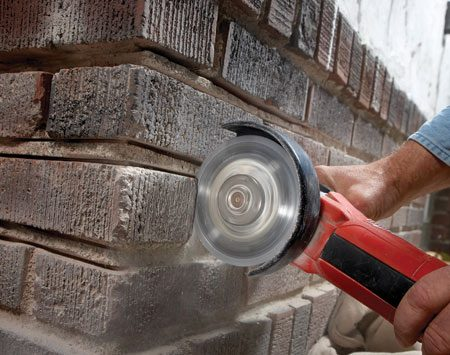 <b>Photo 2: Plunge-cut the vertical joints</b></br> Grind both sides of the vertical joints. Plunge the grinder into the joint and work it up and down to make the cuts. But be careful not to grind the bricks above and below the joints.