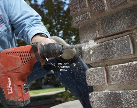 <b>Photo 3: Hammer out the mortar</b></br> Keep moving the rotary hammer drill along the joints as you chisel out the mortar. Be sure to keep the chisel off the bricks so you don't knock them out of place.