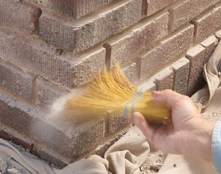 <b>Photo 4: Sweep out the joints</b></br> Use a small broom to sweep debris and dust out of the joints. Inspect the joints for any remaining stubborn mortar and knock it out with the drill.