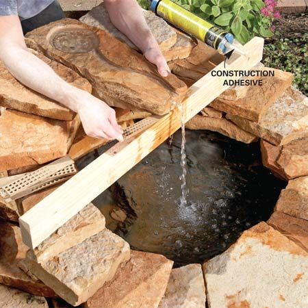 "<b>Photo 8: Set the stone</b></br> Run the pump and adjust the stone until you get a strong stream. Shims and a 2x4 ""bridge"" hold the fountain stone in position until the adhesive or mortar hardens."
