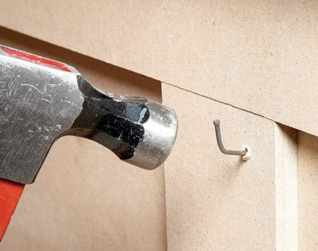 <b>Power nailers work best</b></br> <p>Unless you're willing to drill a hole   for every single nail, don't plan on   using a hammer. Without a hole, the   nail will probably bend in rock-hard   MDF. And even if it goes in without   bending, the nail will push up a   mound of fiber that looks like a mini   volcano. A trim nailer, on the other   hand, shoots nails through MDF   every time. The skinny nails will   raise tiny pimples, but you can easily   scrape them off with a sharp putty   knife before you fill the  nail holes. </p>