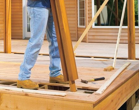 """<b>Plan ahead to anchor the posts</b></br> One good way to lock the posts into the deck is to build a """"socket"""" into the deck framing, then sandwich a 2x4 between 2x6 lumber for the post. Extend the center member of the """"sandwich"""" so it will fit into the socket. Drop the post in and secure it with construction screws to keep the shade structure from lifting off during windy storms and help prevent sway. Then add decorative braces between the posts and the beams at the top."""