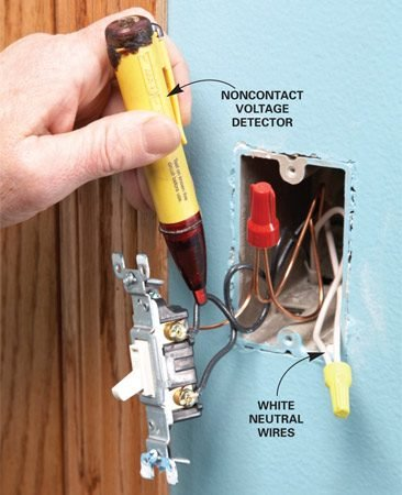 <b>Photo 1: Test for power</b></br> With the power turned off at the main electrical panel, unscrew the switch and pull it out. Turn the power back on and use a noncontact voltage tester to locate the hot wire.