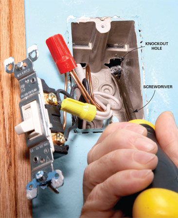 <b>Photo 3: Remove the knockout</b></br> Punch out one of the knockouts in the top of the box with a screwdriver. You'll push the cable through this hole.