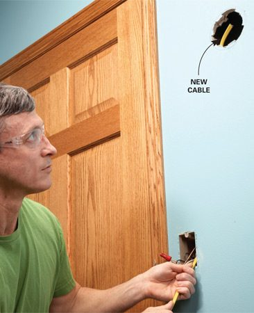 <b>Photo 4: Push in the cable</b></br> Push the cable through the knockout and up toward the hole. If you're lucky, it'll come into sight. Otherwise, reach through the hole to grab it.