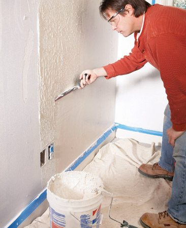 <b>Photo 4: Pull up from the bottom</b></br> Roll joint compound onto the lower section and smooth it by pulling the trowel upward.