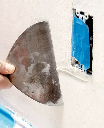 <b>Photo 5: Scrape off lumps</b></br> Scrape the wall with a 6-in. putty knife to remove lumps and ridges. Brush off the wall and you're ready for the next coat.