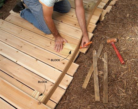 <b>Photo 10: Mark curves for cutting</b></br> Mark the curves on decking using the hardboard siding. Hold the siding in place with stakes or blocks or by hand.