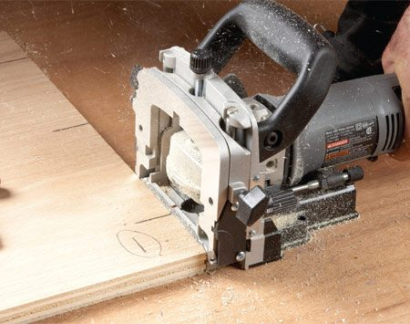 <b>Photo 2: Rest the base of the joiner on the bench</b></br> To cut accurate slots, rest the biscuit joiner on the workbench instead of the fence. It's more stable and doesn't require any setup.