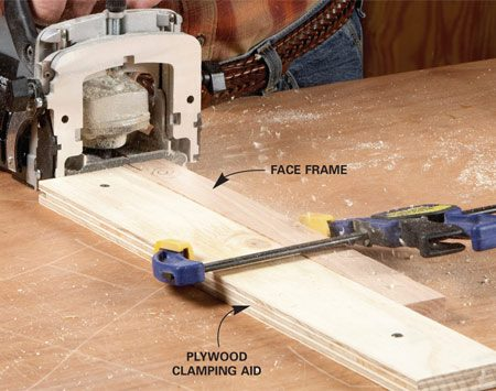 <b>Photo 2: Screw plywood to the bench as a clamping aid</b></br> Line up the end of the part with the end of the clamping board and clamp the two together. The wide end makes a stable surface to press the biscuit joiner against.