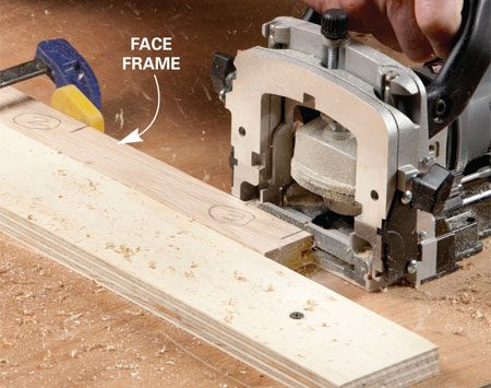 <b>Photo 3: Cut the side slot</b></br> Align the center marks and cut the biscuit slots. The clamping block makes a solid surface to push against.