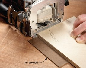 <b>Photo 2: Don't adjust the fence—use spacers</b></br> Instead of adjusting the fence to cut slots in thinner material, add a spacer underneath. You'll get great results as long as you use the same spacer when you cut the slots in the adjoining panel (see Photo 3).