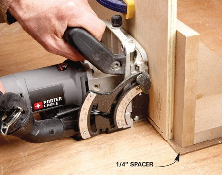 <b>Photo 3: Place the spacer under the end of the panel</b></br> Make sure the spacer doesn't protrude past the face of the panel. Then rest the base of the biscuit joiner on the workbench when you cut the slots.