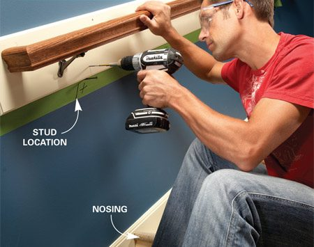 <b>Photo 2: Screw the board to the studs</b></br> Position a strip of masking tape parallel to the stairs with the top edge located so that the top of the rail will be 34 to 36 in. above the stair nosings. Locate the studs and mark them on the tape. Support the handrail board on a pair of nails. Drive a pair of 3-in. screws into every other stud.