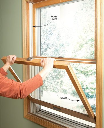 <b>Photo 1: Remove the sash</b></br> Push in on the jamb liner while you pull out on the top corner of the sash. Release the opposite side using the same technique. Then pivot the sash downward and tilt it sideways to remove it.