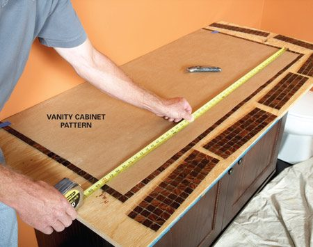 <b>Photo 1: Design the top to avoid cutting tile</b><br/>Cut a paper pattern the size of the vanity cabinet and lay it over the tile. That makes it easy to size the top for full tiles.