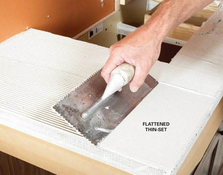 <b>Photo 4: Comb out, then flatten the thin-set</b></br> Use a 3/16-in. V-notch trowel to spread a layer of thin-set over the backer board. Then flatten it with the straight side of the trowel.