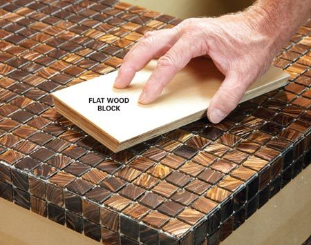 <b>Photo 6: Embed the tile with a wood block</b><br/>Tap the top of the mosaic tile with a flat block of wood to level the surface and ensure a secure bond with the thin-set.