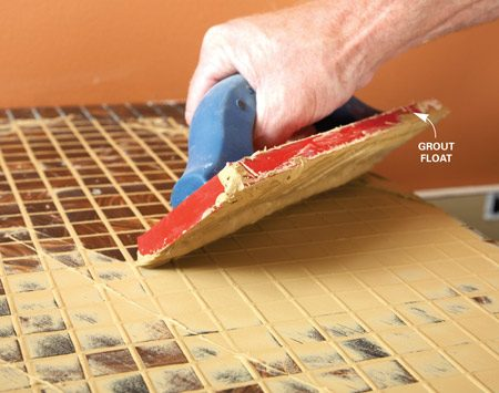 <b>Photo 7: Grout the tile</b><br/>Work the grout back and forth in different directions to completely fill the joints and eliminate voids. Well-packed joints are the key to a lasting grout job.